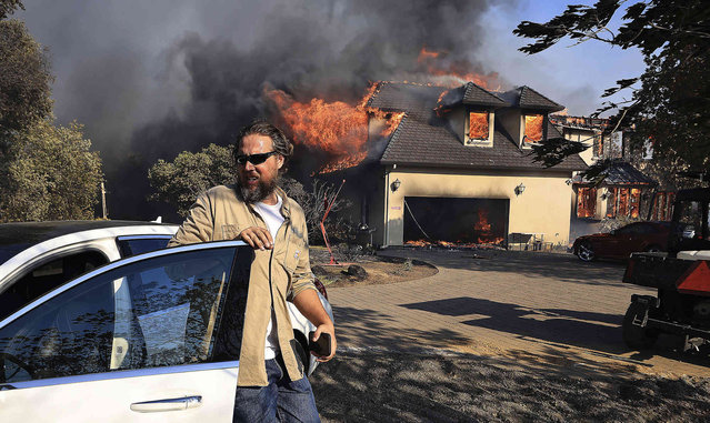 Joe Kikuchi, of Pacific Gas and Electric, moves two cars to safety as a house in Marina Estates above Lake Mendocino burns during the Hopkins fire Sunday, September 12, 2021, near Calpella, Calif. (Photo by Kent Porter/The Press Democrat via AP Photo)