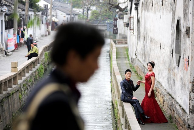 A man walks past a newly wed couple posing for wedding photos near the Song Dynasty's Pingjiang street built along a canal in Suzhou in east China's Jiangsu province Thursday, April 16, 2015. Pingjiang street was built along a canal and existed as early as the Song Dynasty, and is one of the famous tourist attractions in the country. (Photo by Andy Wong/AP Photo)