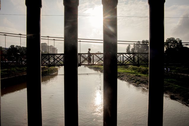 A person crosses a suspension bridge in an early morning in Kathmandu, Nepal, 10 August 2021. (Photo by Narendra Shrestha/EPA/EFE)