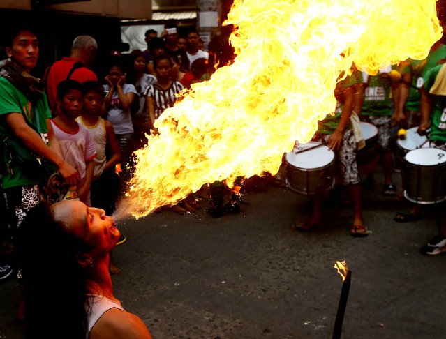 A fire-eater performs on the street during Chinese New Year celebrations, Saturday, January 28, 2017, in the Chinatown area of Manila, Philippines. Chinese around the world are celebrating this year's Year of the Rooster according to the Chinese zodiac calendar. (Photo by Bullit Marquez/AP Photo)
