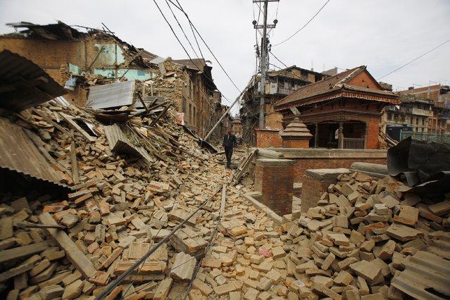 A Nepalese man walks through destruction caused by Saturday's earthquake, in Bhaktapur, Nepal, Sunday, April 26, 2015. (Photo by Niranjan Shrestha/AP Photo)