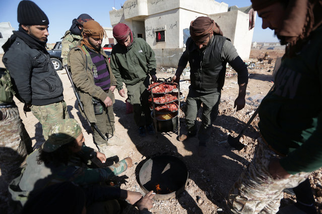 Rebel fighters carry meat to be cooked inside a hole in the ground on the outskirts of Al-Bab town in Syria January 22, 2017. (Photo by Khalil Ashawi/Reuters)