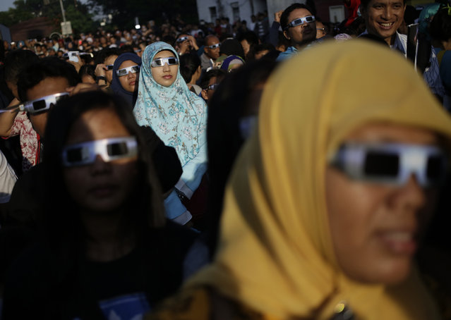 People look up at the sun wearing protective glasses to watch a solar eclipse in Jakarta, Indonesia, Wednesday, March 9, 2016. The rare astronomical event is being witnessed Wednesday along a narrow path that stretches across 12 provinces encompassing three times zones and about 40 million people. (Photo by Dita Alangkara/AP Photo)