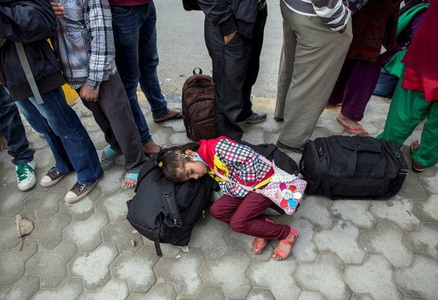 A girl sleeps on her family's belongings as others wait to board buses to leave Kathmandu following Saturday's earthquake in Nepal, April 29, 2015. (Photo by Danish Siddiqui/Reuters)