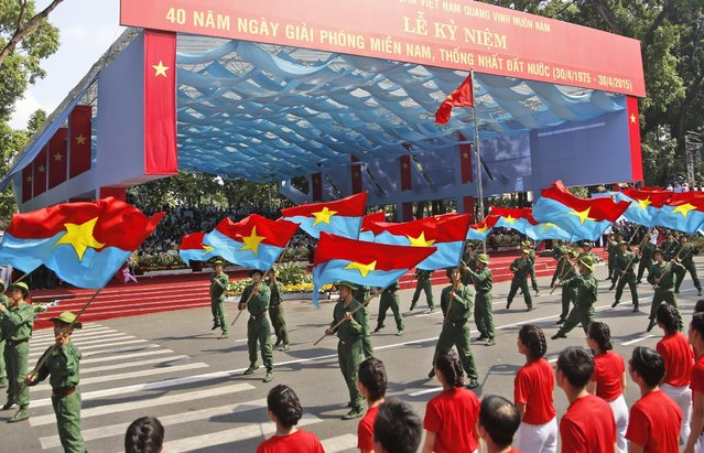 """Performers wave the National Liberation Front flags during a parade celebrating the 40th anniversary of the end of the Vietnam War which is also remembered as the """"Fall of Saigon"""", in Ho Chi Minh City, Vietnam, Thursday, April 30, 2015. (Photo by Dita Alangkara/AP Photo)"""