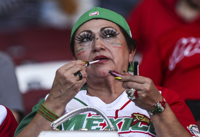 In this Wednesday, February 1, 2017 photo, a Mexican baseball fan touches up her lipstick while watching a Caribbean Series game between Cuba's Granma and the Dominican Republic's Licey Tigers, in Culiacan, Mexico. Culiacan's Tomateros Stadium is host to the 2017 Series featuring Puerto Rico, Dominican Republic, Cuba and Mexico, from Feb. 1 through Feb. 7. (Photo by Luis Gutierrez/AP Photo)