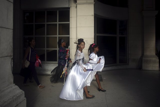 Children walk in downtown Havana after performing a dance in a public park, February 24, 2016. (Photo by Alexandre Meneghini/Reuters)