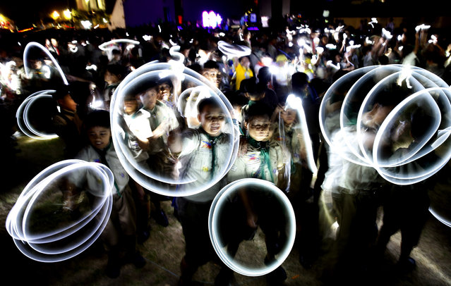 Philippine Boy Scouts play with their flashlights at the countdown for the 12th Earth Hour event Saturday, March 30, 2019 in suburban Makati city east of Manila, Philippines. Earth Hour is the symbolic switching off of the lights for one hour to help minimize fossil fuel consumption as well as mitigate the effects of climate change. (Photo by Bullit Marquez/AP Photo)