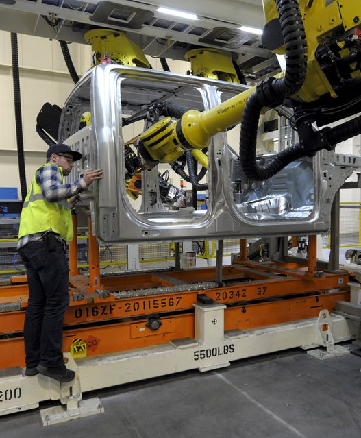 Auto worker Jared Eudier checks a seam on an F150 cab at Ford's Kansas City Assembly Plant where new aluminum intensive Ford F-Series pickups are built in Claycomo, Missouri May 5, 2015. (Photo by Dave Kaup/Reuters)