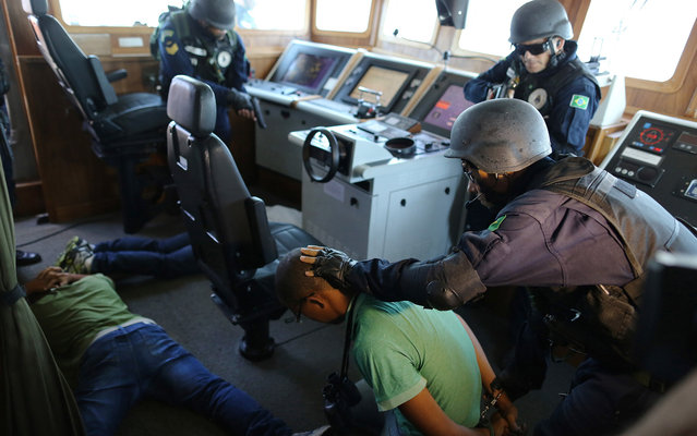 Brazilian Marines practice raiding a ship during a military exercise in Guanabara Bay, in Rio de Janeiro, Brazil, Wednesday, February 20 2014. Brazil's Navy said that the operations being carried out this week in preparation for the 2014 FIFA World Cup are the largest exercises in its history. (Photo by Leo Correa/AP Photo)