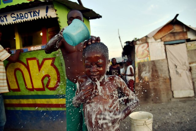 Beloni (34) gives a bath to his son, 6, on a small street in the neighborhood of Cite Vincent, on March 21, 2016 in the commune of Cite Soleil in the Haitian capital Port-au-Prince. World Water Day, marked on March 22, 2016, is an international observance to learn more about water related issues and to take action for sustainable management of freshwater resources. (Photo by Hector Retamal/AFP Photo)