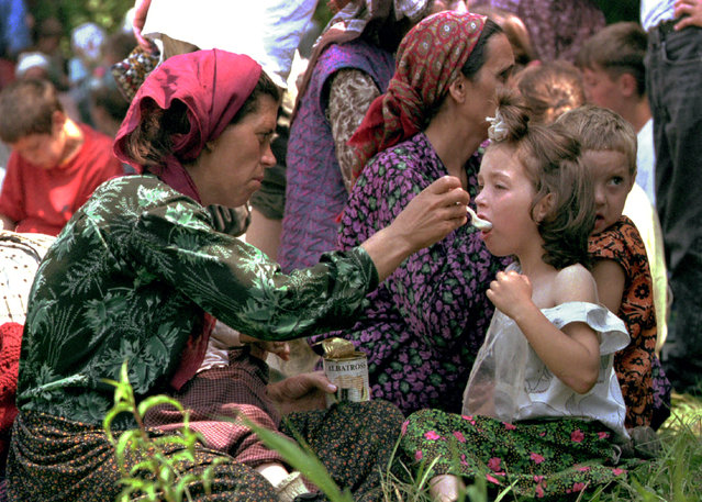 A mother feeds her child at the refugee camp outside the U.N. compound at Tuzla Airport, where thousands of refugees were arriving after fleeing the U.N. safe-haven in Srebrenica after it was overrun by Bosnian Serbs, July 1995. (Photo by Reuters)