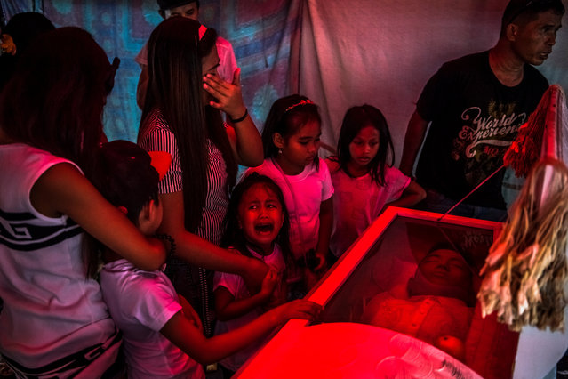 """Six-year-old Jimji cries in anguish as she screams """"papa"""" before funeral parlor workers move the body of her father, Jimboy Bolasa, from the wake at the start of the funeral to Navotas Cemetery in Manila, Philippines. Unidentified men abducted Mr. Bolasa and a neighborhood friend one night. Less than an hour later, their beaten bodies, with signs of torture and gunshot wounds, were dumped under a nearby bridge. The police claim the men were alleged drug dealers while their family members say they had only surrendered themselves. (Photo by Daniel Berehulak/Reuters/The New York Times/Courtesy of World Press Photo Foundation)"""
