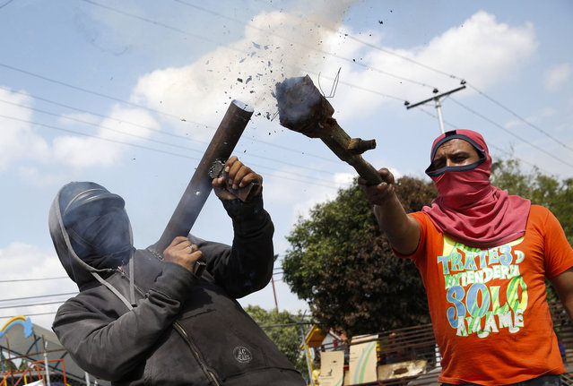 An opposition demonstrator shoots a rudimentary mortar during a protest against President Nicolas Maduro's government in Rubio outside San Cristobal, about 410 miles (660 km) southwest of Caracas, February 27, 2014. (Photo by Carlos Garcia Rawlins/Reuters)