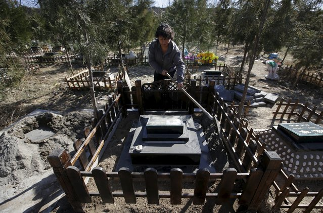 Baifu pet cemetery worker Du Huanying decorates a new pet tomb ahead of the Qingming Festival on the outskirts of Beijing, China March 27, 2016. (Photo by Jason Lee/Reuters)