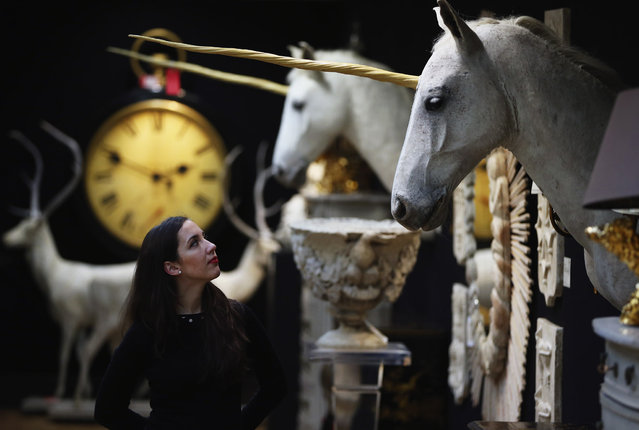 """A Christie's employee poses in front of one of two """"Unicorn Heads"""" at Christie's auction house on March 3, 2014 in London, England. The items make up part of the Les Trois Garcons' collection which will be sold at auction on March 5, 2014 at their Knightsbridge auction house. The collection is made up of 380 lots from the owners of 'Les Trois Garcons' celebrity restaurant in Shoreditch and their homes. (Photo by Dan Kitwood/Getty Images)"""