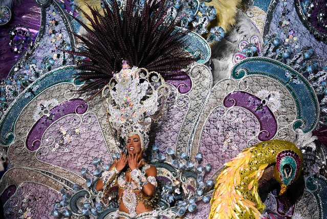 A nominee for queen of the Carnival of Santa Cruz shows off her outfit on the main stage in Santa Cruz de Tenerife on the Spanish Canary island of Tenerife on February 22, 2017. The costumes are more than five meters high and over 80 kilos in weight. The event began on February 1 and finishes on March 5 with orchestras playing Caribbean and Brazilian rhythms throughout the festivities that range from elections for the Carnival Queen, the Junior Queen and the Senior Queen, to children and adult murgas (satirical street bands), comparsas (dance groups) and street performances. (Photo by Desiree Martin/AFP Photo)