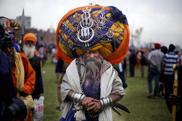 "A Sikh warrior, wearing a huge turban attends the annual fair of ""Hola Mohalla"" in Anandpur Sahib, in the northern Indian state of Punjab, Monday, March 17, 2014. Believers from various parts of northern India collect at the religious fair to celebrate the festival of Holi in a tradition set by the tenth Sikh guru Guru Gobind Singh in the seventeenth century. Nihangs, or Sikh warriors, display their martial skills and attire during the fair, believed to be maintained in the exact tradition as set by the Guru. (Photo by Altaf Qadri/AP Photo)"