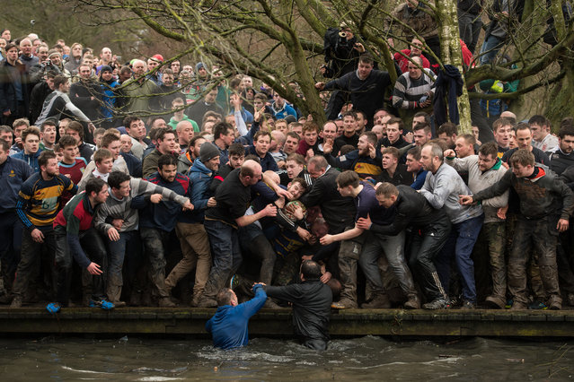 Competitors from the opposing teams, the Up'ards and the Down'ards, reach for the ball during the annual Royal Shrovetide Football Match in Ashbourne, northern England, on February 28, 2017. The mass-participation ball game involves two teams, whose players are defined by which side of a small brook that bisects the town they were born, aiming to score a goal, which are some three miles apart. The game, which has very few rules, is played over two 8 hour periods on Shrove Tuesday and Ash Wednesday. Royal Shrovetide Football is believed to have been played annually in Ashbourne since 1667. (Photo by Oli Scarff/AFP Photo)