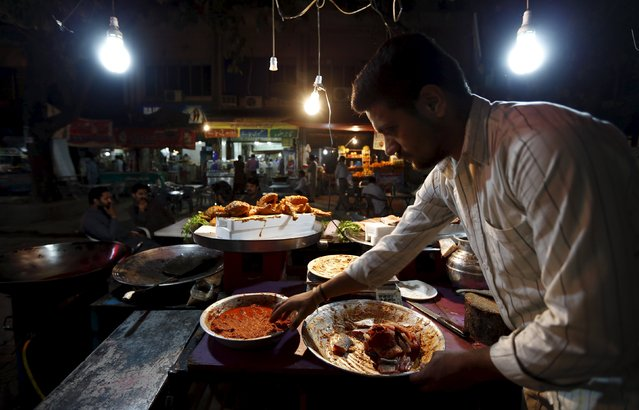 A man prepares fish under lights powered by a generator at his stall in Islamabad April 9, 2015. After ordering summer dress code and switching off air-conditioners in offices, the Pakistani government has reintroduced a plan to beat the energy crisis in Islamabad – shops and restaurants must close earlier. (Photo by Caren Firouz/Reuters)