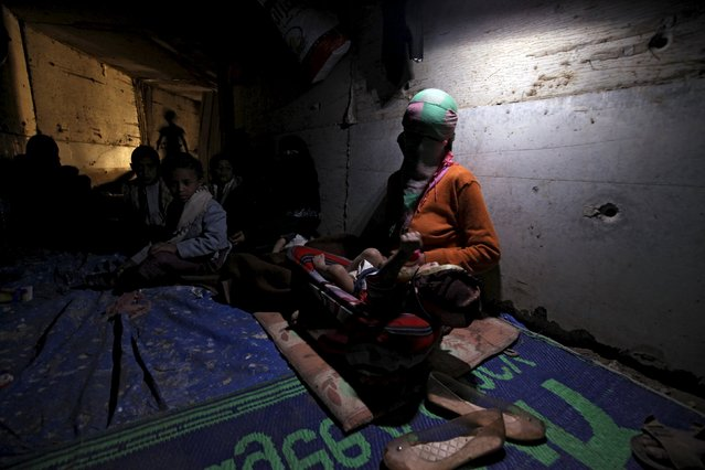 A woman holds her daughter inside an underground water tunnel with other displaced Yemeni families, after they were forced to flee their home due to ongoing air-strikes carried out by the Saudi-led coalition in Sanaa May 2, 2015. (Photo by Mohamed al-Sayaghi/Reuters)