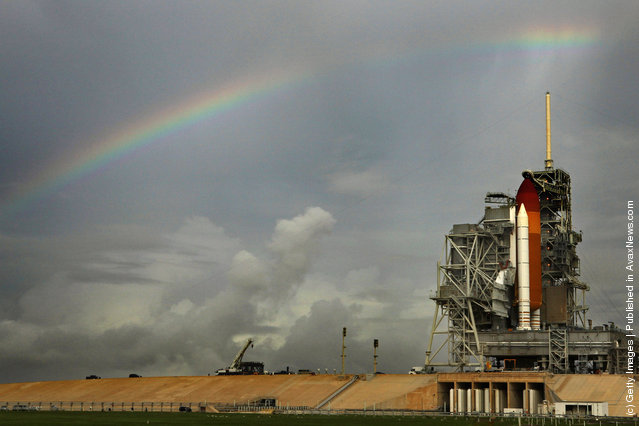 Rainy skies produce a rainbow over the space shuttle Atlantis as it stands on launch pad 39A one day before its scheduled launch at Kennedy Space Center