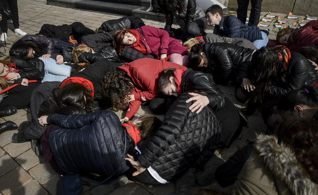 "Women lay on the ground during a performance to raise awareness for the plight of women killed by their partners in Romania, marking the International Women's Day in Bucharest, Romania, Wednesday, March 8, 2017. Dozens of women lay on the ground and read out names of women, aged 16 to 66, killed by their partners in Romania in an event called ""If one falls, we all fall"". (Photo by Andreea Alexandru/AP Photo)"
