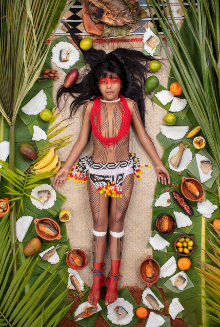 "Kawakanih Yawalapiti, 9, Upper Xingu region of Mato Grosso, Brazil, 2018: Kawakanih lives with her tribe, the Yawalapiti, in Xingu national park, a preserve in the Amazon basin of Brazil. The Yawalapiti collect seeds to preserve species unique to their ecosystem, which lies between the rain forest and savannah. Kawakanih's diet is simple, consisting mainly of fish, cassava, porridge, fruit and nuts. ""It takes five minutes to catch dinner"", says Kawakanih. ""When you're hungry, you just go to the river with your net"". (Photo by Gregg Segal/The Guardian)"