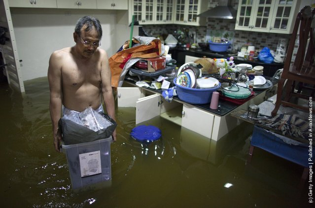 A flood victim carries water damaged belongings out from inside the kitchen in his flooded condo complex near the Chao Phyra river