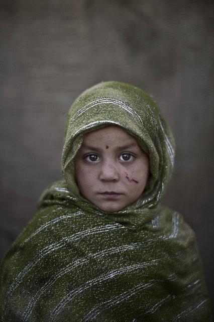 In this Monday, January 27, 2014 photo, Afghan refugee girl, Madina Juma'a, 4, poses for a picture, while playing with other children in a slum on the outskirts of Islamabad, Pakistan. (Photo by Muhammed Muheisen/AP Photo)