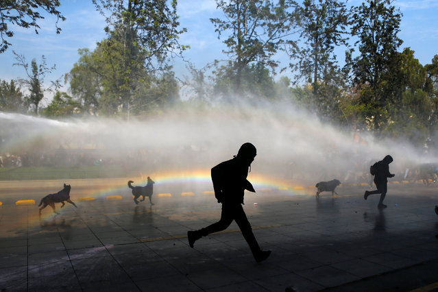 Student protesters run away as a riot police vehicle releases a jet of water during a demonstration to demand changes in the education system in Santiago, Chile, April 21, 2016. (Photo by Ivan Alvarado/Reuters)