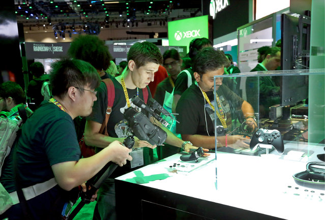 E3 2015 attendees interact with the Xbox Elite Wireless Controller at the Xbox booth at E3 in Los Angeles on Tuesday, June 16, 2015. (Photo by Casey Rodgers/Invision for Microsoft/AP Images)