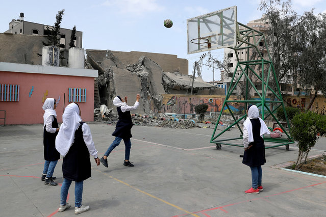 Palestinian students play basketball inside their damaged school nearby a building that was destroyed by Israeli air strikes, in Gaza City on May 7, 2019. (Photo by Mohammed Salem/Reuters)