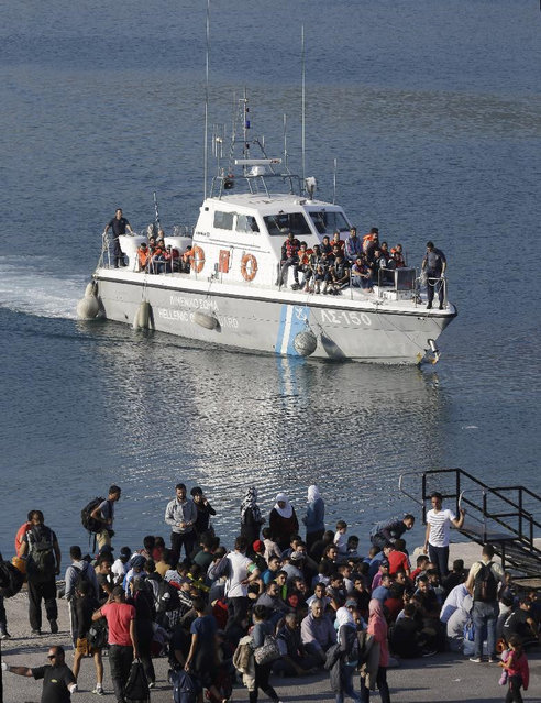 A Greek Coast Guard vessel arrives with migrants after an operation as other migrants who arrived earlier wait to be counted by Greek authorities at the port of Mitylene on the northeast Greek island of Lesvos Wednesday, June 17, 2015. Around 100,000 migrants have entered Europe so far this year as Italy and Greece have borne the brunt of the surge with many more migrants expected to arrive from June through to September. (AP Photo/Thanassis Stavrakis)