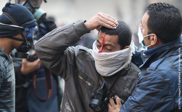 An injured protestor  is led away during clashes with police near Tahrir Square