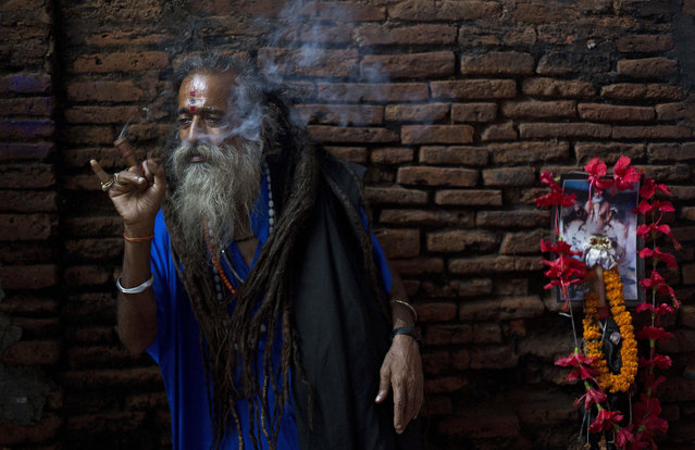 A Sadhu, or Hindu holy man, smokes at the Kamakhya temple in Gauhati, India, Tuesday, June 23, 2015. Hundreds of Sadhus, or Hindu holy men, have arrived for the five-day festival to perform rituals at the temple during the annual Ambubasi festival that began Monday. (Photo by Anupam Nath/AP Photo)