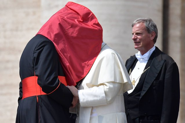 A gust of wind lifts the mantilla of an unidentified cardinal as he shakes hands with Pope Francis at the end of an audience as part of the Jubilee Year of Mercy on April 30, 2016 at St Peter's square in Vatican. (Photo by Tiziana Fabi/AFP Photo)