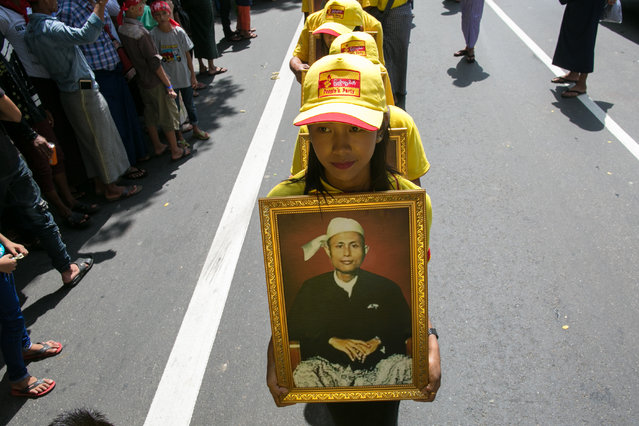 Girls parade with a portrait of General Aung San during the Martyrs' Day ceremony in Yangon on July 19, 2019. Myanmar observes the 72nd anniversary of Martyrs' Day on July 19, marking the assassination of independence heroes including Aung San Suu Kyi's father, who helped end British colonial rule. (Photo by Sai Aung Main/AFP Photo)