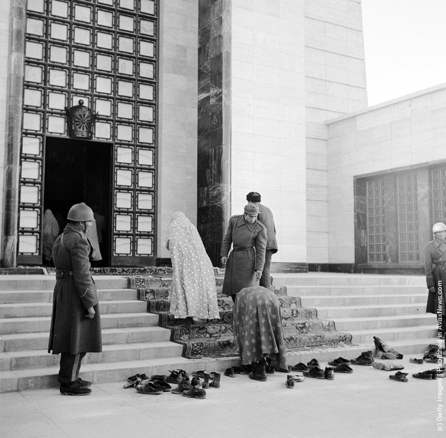 1950:  A woman taking off her shoes and leaving them with a pile of others at the entrance to the former Shah of Persia's Mausoleum which is guarded by soldiers