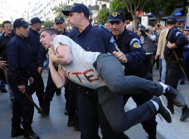 """Algerian police arrest a protestor from the Barakat movement (meaning in Algerian Arabic """"That's enough""""), as they demonstrate in Algiers on April 16, 2014 against Algeria's current President Bouteflika Abdelaziz running for a fourth term in the presidential elections. More than 260,000 police have deployed across the country to guarantee security in the 50,000 polling booths set up to accommodate the 23 million Algerians eligible to vote in the presidential race, which is being contest by six candidates. (Photo by Farouk Batiche/AFP Photo)"""