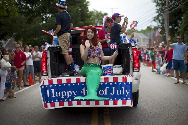 A girl dressed as a mermaid rides on the back of a pickup truck through Barnstable Village on Cape Cod, during the annual Fourth of July Parade celebrating the country's Independence Day, in Barnstable, Massachusetts, July 4, 2015. (Photo by Mike Segar/Reuters)