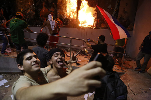 Men pose for a photo outside the congress building during clashes between police and protesters opposing an approved proposed constitutional amendment that would allow the election of a president to a second term, in Asuncion, Paraguay, Friday, March 31, 2017. Some protesters broke through police lines and entered the first floor, where they set fire to papers and furniture. Police used water cannon and fired rubber bullets to drive demonstrators away from the building while firefighters extinguished blazes inside. (Photo by Jorge Saenz/AP Photo)