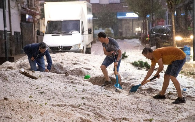 "People remove hail in Arganda del Rey, Madrid, Spain, 26 August 2019. Spanish Meteorological Agency (Aemet) has activated the orange warning by ""important risk"" due to heavy rains. (Photo by Rodrigo Jimenez/EPA/EFE/Rex Features/Shutterstock)"