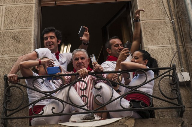 """People look on from a balcony while they celebrate during the launch of the """"Chupinazo"""" rocket, to celebrate the official opening of the 2015 San Fermin Fiestas, in Pamplona, northern Spain, Monday, July 6, 2015. (Photo by Alvaro Barrientos/AP Photo)"""