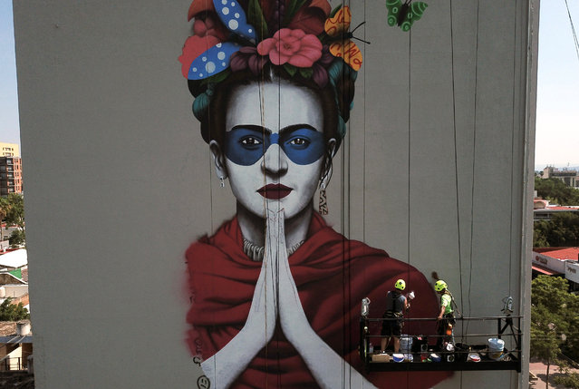 """Irish urban artist Fin Dac (2-R) and his assistant work on his mural """"Magdalena"""", in honor of Mexican painter Magdalena Carmen Frida Kahlo in the month of her birth, in Guadalajara, Jalisco state, Mexico, on July 9, 2019. (Photo by Ulises Ruiz/AFP Photo)"""