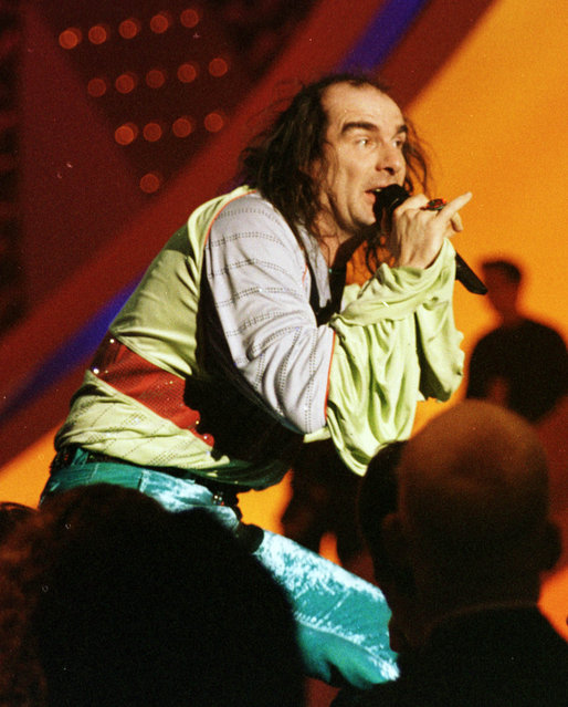 In this Saturday, May 9, 1998 file photo, Germany's Guildo Horn performs on stage in the final dress rehearsal ahead of the final. Horn, a cult figure in Germany, made waves in 1998 with his velvet trousers, platform shoes and ruffled shirt. He rushed across the stage, playing cowbells and climbing up on the scaffolding, too. Similar eccentricities are expected at this year's event in the Swedish capital of Stockholm, the final of which takes place on Saturday, May 14. (Photo by Louisa Buller/AP Photo)