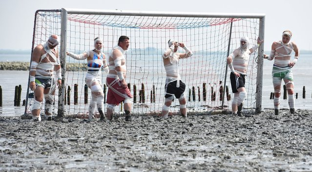 """Players attend the start of their soccer match at the so called """"Wattoluempiade"""" (Mud Olympics) in Brunsbuettel at the North Sea, July 11, 2015. (Photo by Fabian Bimmer/Reuters)"""