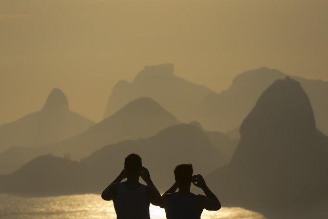 People photograph the sunset in Rio de Janeiro, Brazil, Sunday, January 6, 2013. (Photo by Felipe Dana/AP Photo)