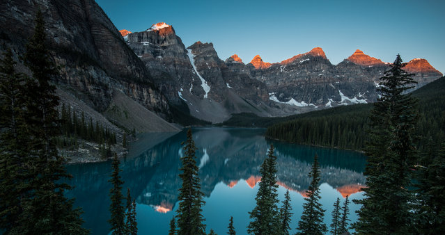 """First Light over the Lake"". In July in Alberta, Canada overlooking beautiful Lake Moraine. First light is around 6:15AM and the sun catching the top of the mountains surrounding the lake is magnificent. Shot with a Nikon D800E on a tripod with a 14mm lens. To capture this image, you need to climb to the top of the rock pile before sunrise. Photo location: Lake Moraine, Alberta, Canada. (Photo and caption by Jeffrey Landman/National Geographic Photo Contest)"