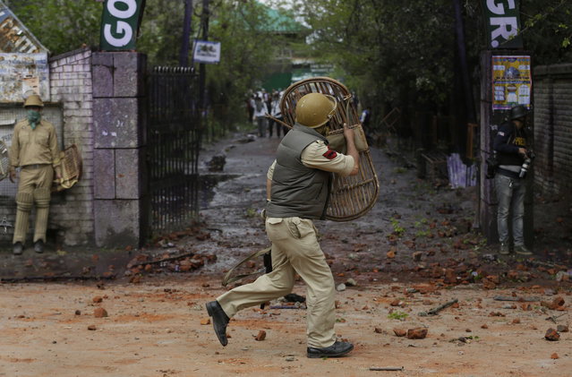 An Indian police man covers himself with a bamboo shield to protect himself from stones thrown by student protestors as they clash in Srinagar, Indian controlled Kashmir, Monday, April 24, 2017. Tensions between Kashmiri students and Indian law enforcement have escalated since April 15, when government forces raided a college in Pulwama, about 30 kilometers (19 miles) south of Srinagar, to scare anti-India. (Photo by Mukhtar Khan/AP Photo)